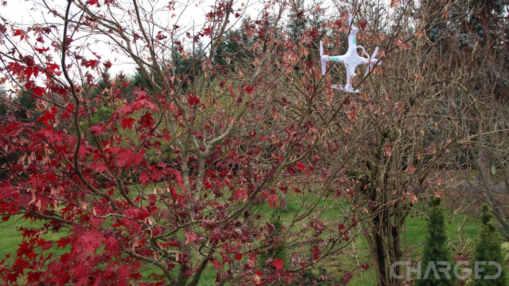The toy drone Syma X5C explorer crashed into a tree and his hanging sideways from a branch, the image tells the story of the title Best drone for beginners - crash and learn